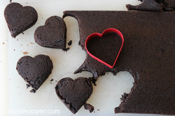 Heart Brownies with Raspberry Buttercream filling- A fudgy brownie in a heart shape filled with a yummy raspberry buttercream filling. Perfect for Valentines Day!