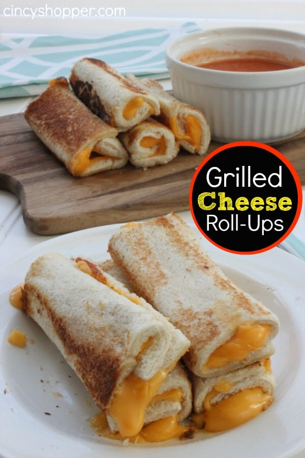photo of 4 stacked grilled cheese rollups with more rollups in the background