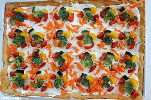 Veggie Pizza Bites- Crescent crust topped with ranch dip mixture then loaded with veggies. Perfect cold bite sized appetizer.