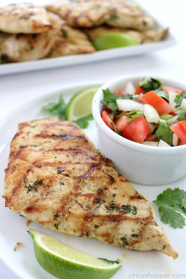 The marinade for this Cilantro Lime Grilled Chicken is so simple to make! We marinade our chicken breasts in cilantro, lime, and a few other ingredients. Then we toss them on the grill to cook them up. Perfect chicken recipe for summer grilling.