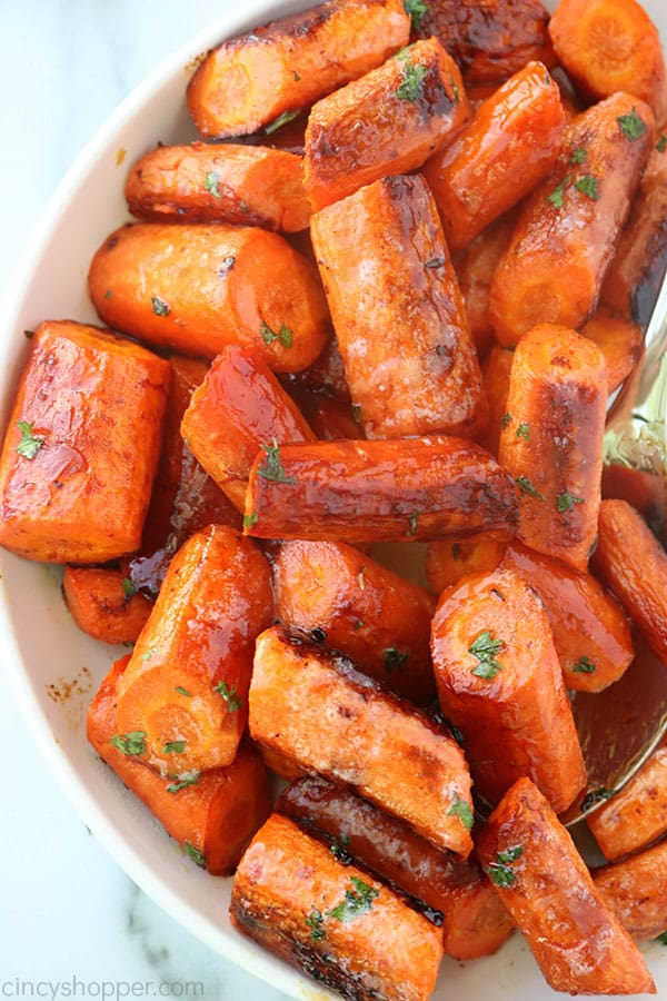 Roasted carrots in a bowl with sppon.