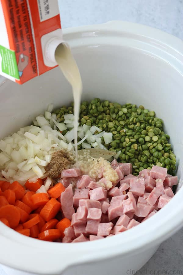 Adding broth to split pea soup in a Crock Pot.