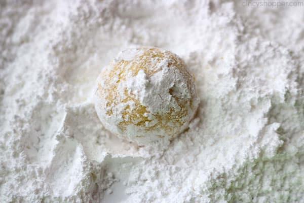 Lemon cookie dough in powdered sugar.