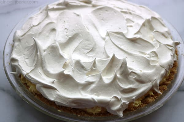 Adding the whipped topping to lemon pie.