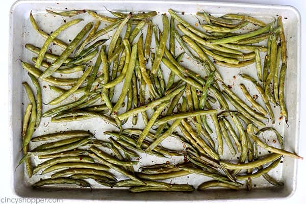Fresh roasted green beans with garlic on a pan.