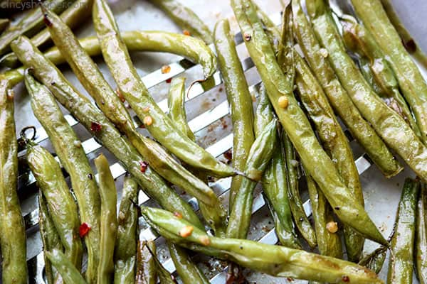 Crispy roasted green beans on a spatula.