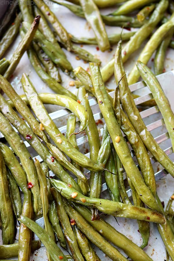 Garlic roasted green beans on a sheet pan with spatula.