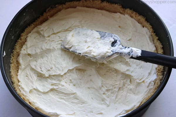 Adding cream cheese topping to crust for no bake lime cheesecake.