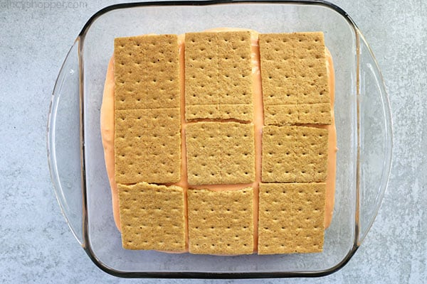 Adding another layer of graham crackers to orange icebox cake.