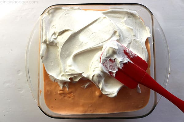 Adding the final whipped topping to Orange Creamsicle Icebox Cake.