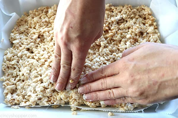 Pressing Rice Krispie mixture into pan.