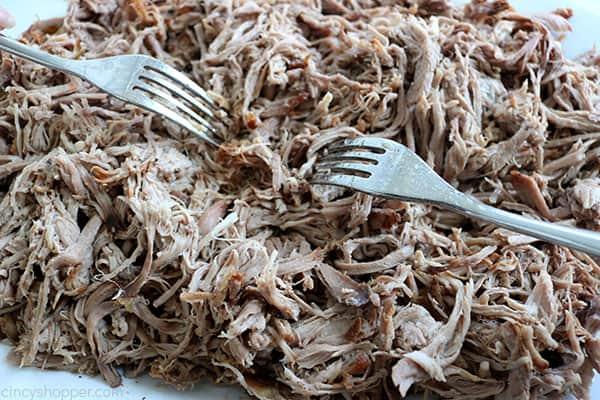 Shredding slow cooker pork with forks.