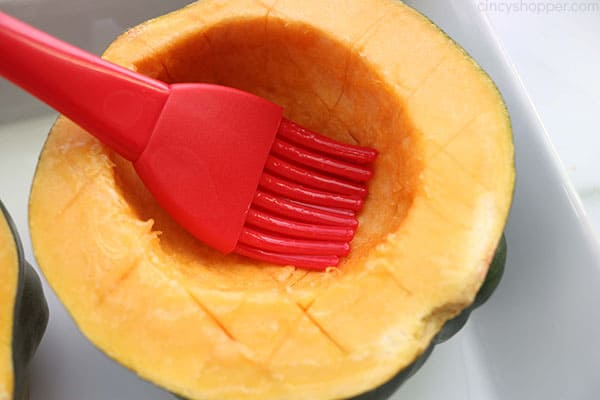 Adding butter to acorn squash.