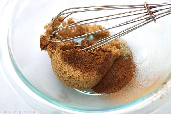 Whisking brown sugar and cinnamon in a clear bowl.