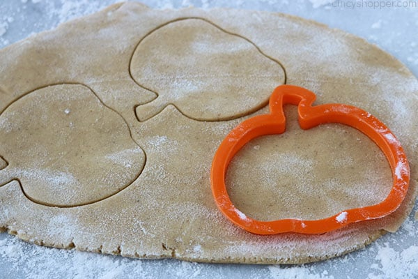 Rolled out pumpkin cookie dough with cookie cutter.