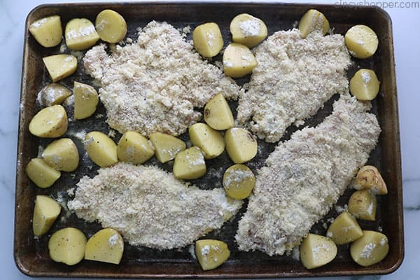 Crusted Ranch Chicken with potatoes on a baking sheet.