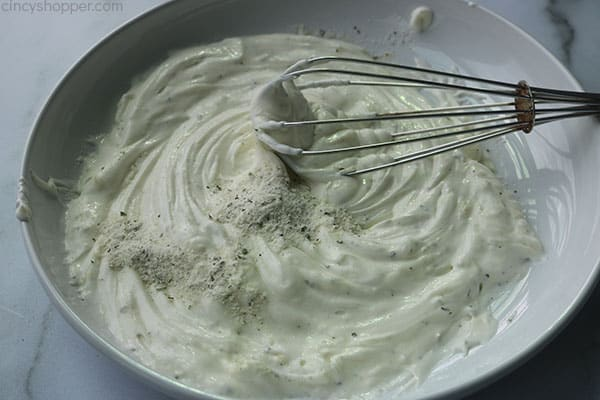 Whisking ranch dressing mix for chicken coating.