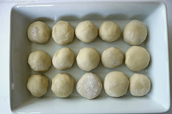 Unbaked dinner rolls in a white baking dish.