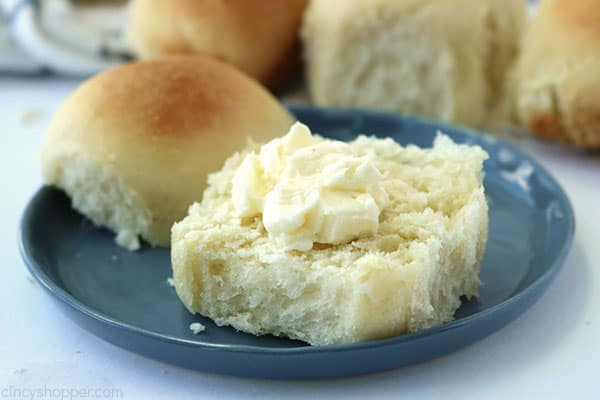 Easy dinner roll swith butter on a blue plate.