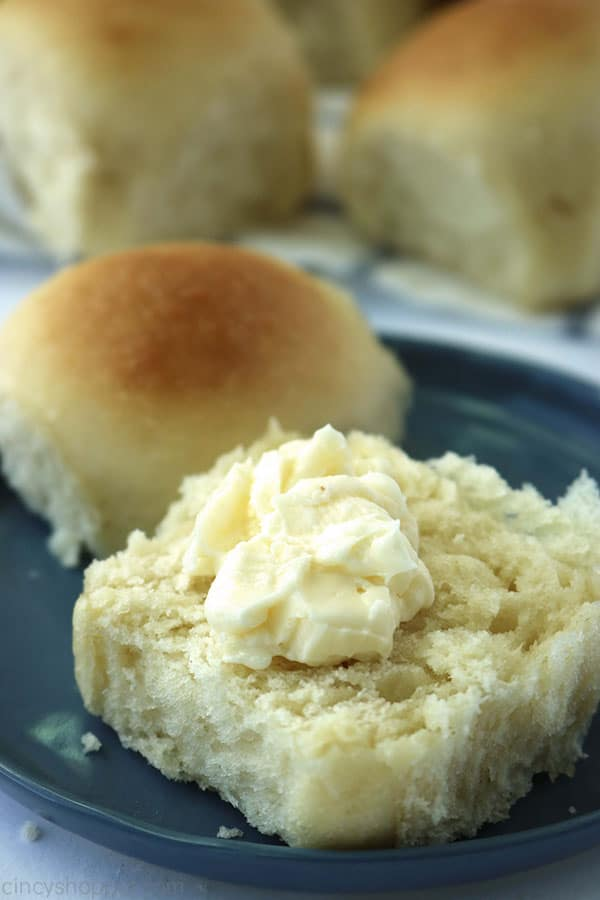 Easy dinner rolls on a plate with butter.