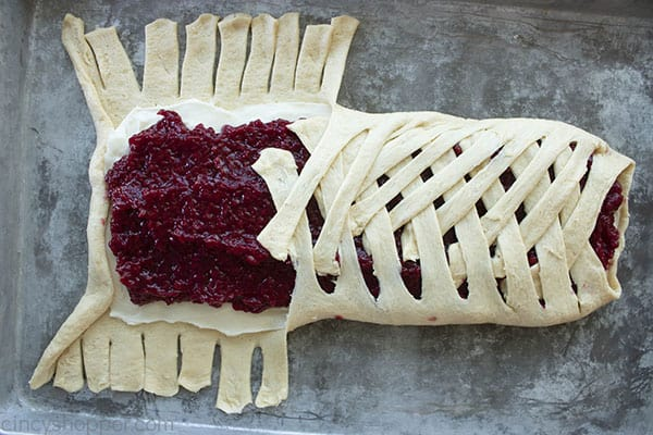 braiding crescent roll dough over cream cheese and raspberry filling