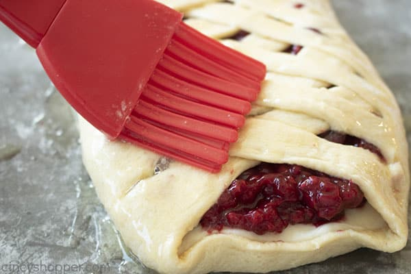brushing melted butter onto braided pastry dough