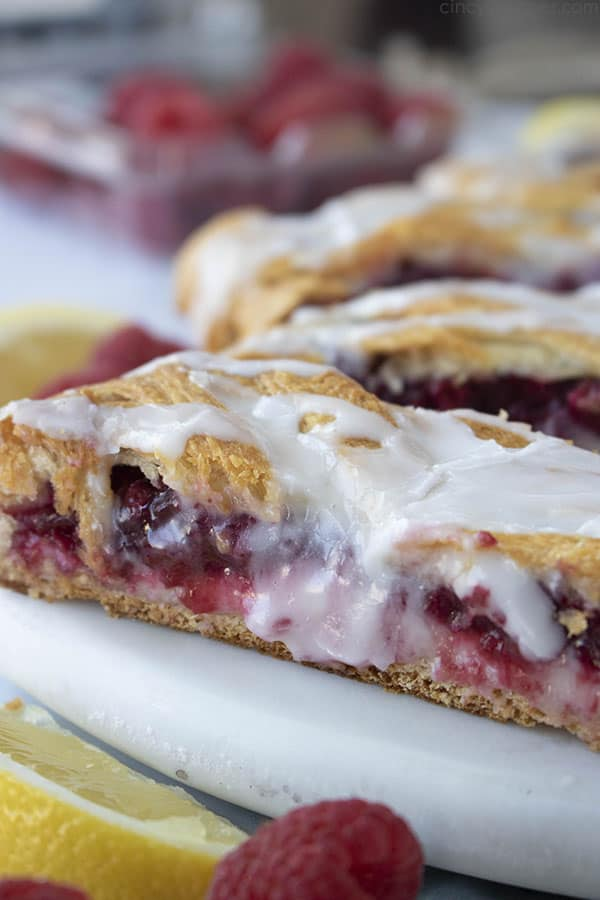 close up slice of crescent roll raspberry pastry with icing