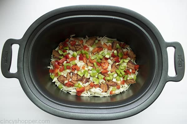 layers of shredded potatoes, bacon, and vegetables in crock pot