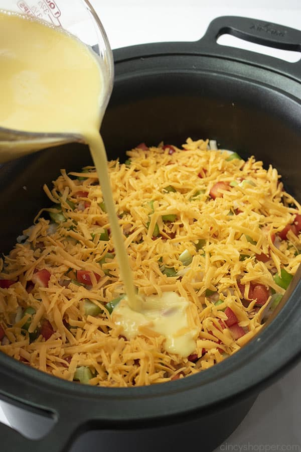 pouring whisked eggs into crock pot to make hashbrown casserole