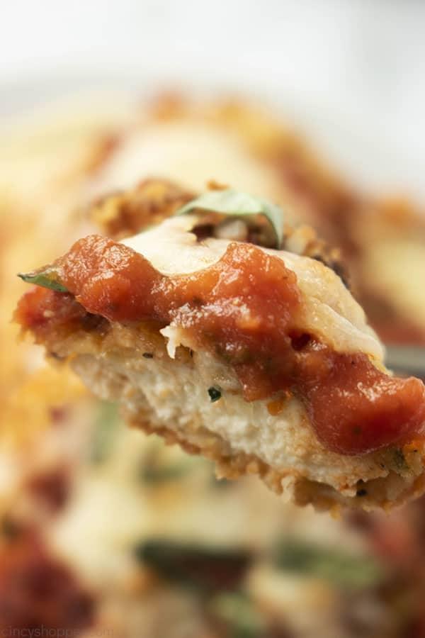 close up of panko coated chicken breast with marinara sauce