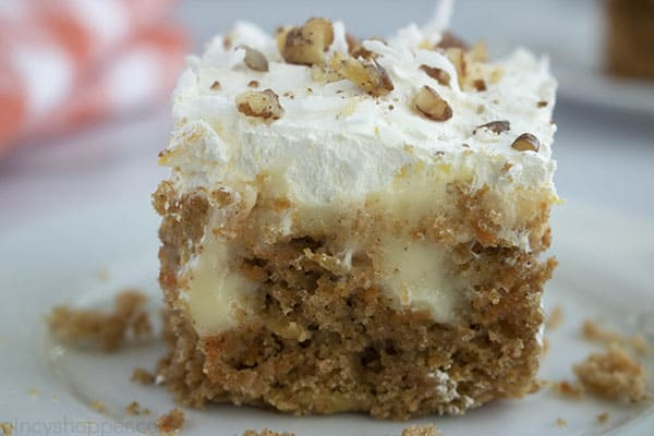 Piece of Carrot Cake poked with cheesecake pudding on a plate.