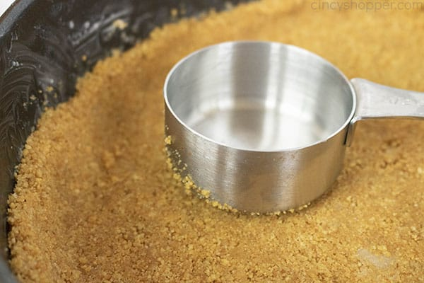 pressing graham cracker crust into a springform pan with a measuring cup