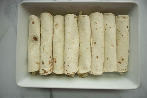 8 rolled enchiladas in a baking dish