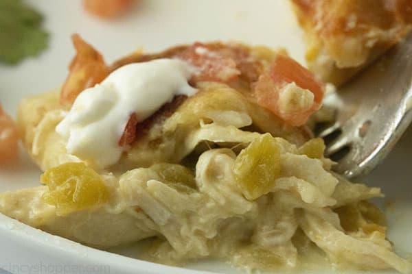 fork full of sour cream chicken enchiladas