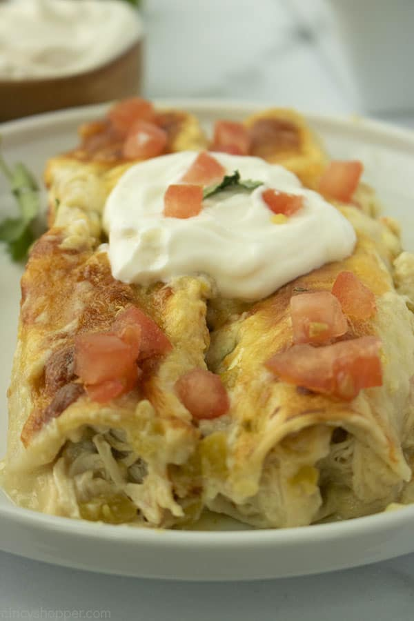 two white chicken enchiladas on a plate with sour cream and tomatoes on top
