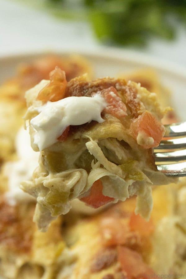 bite of white chicken enchilada on a fork