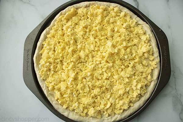 cooked scrambled eggs on pizza crust