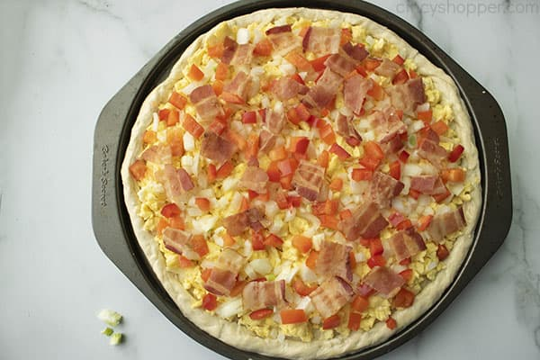 pieces of cooked bacon on top of a breakfast pizza