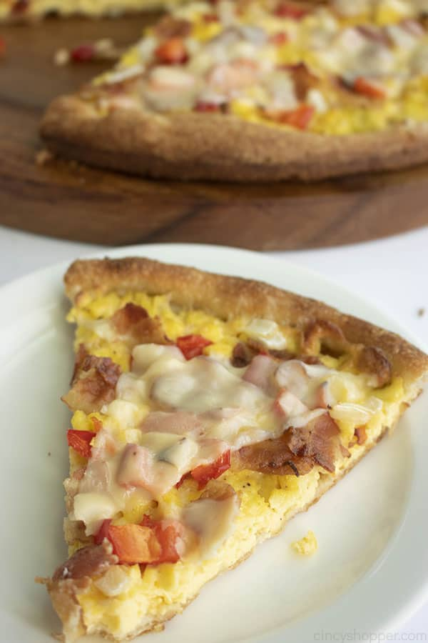 slice of pizza with bacon, eggs and cheese on top