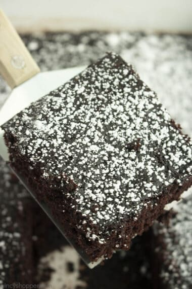 square slice of wacky chocolate cake dusted with powdered sugar