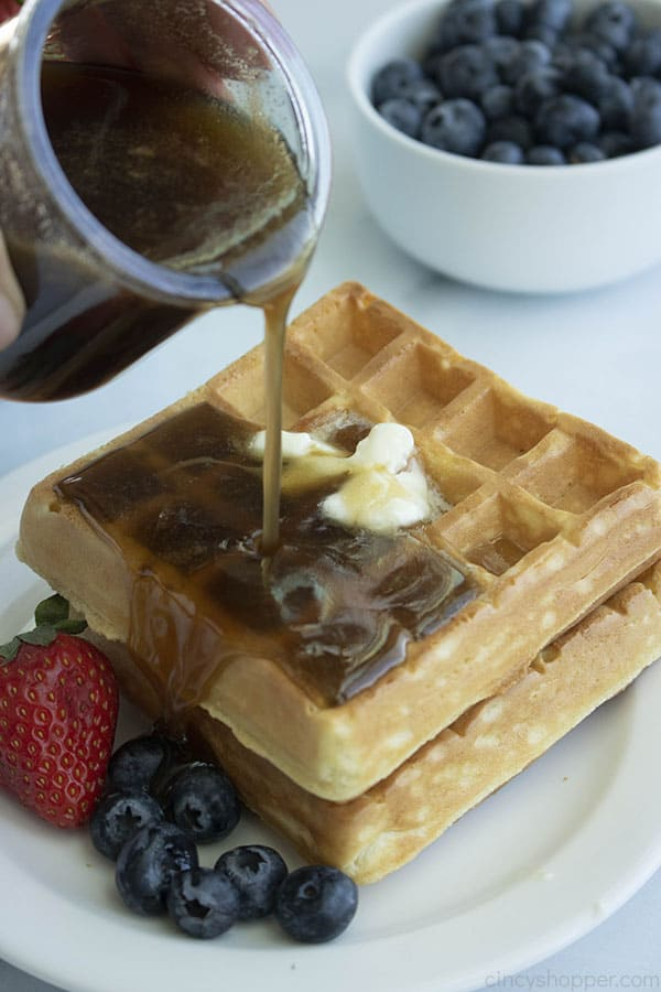 Pouring homemade pancake syrup over waffle.