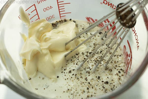 Whisking mayo and ranch dressing in a measuring cup.