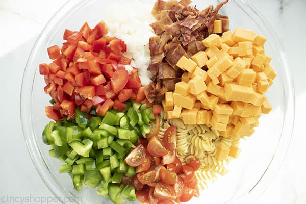 Pasta, bacon and veggies in a large bowl to make pasta salad