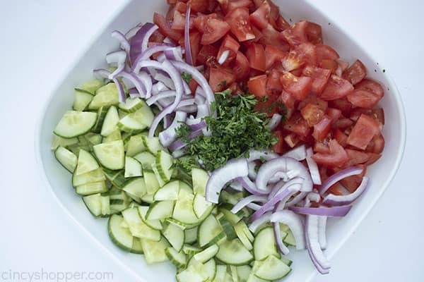 bowl of chopped cucumbers tomatoes and onions with fresh parsley