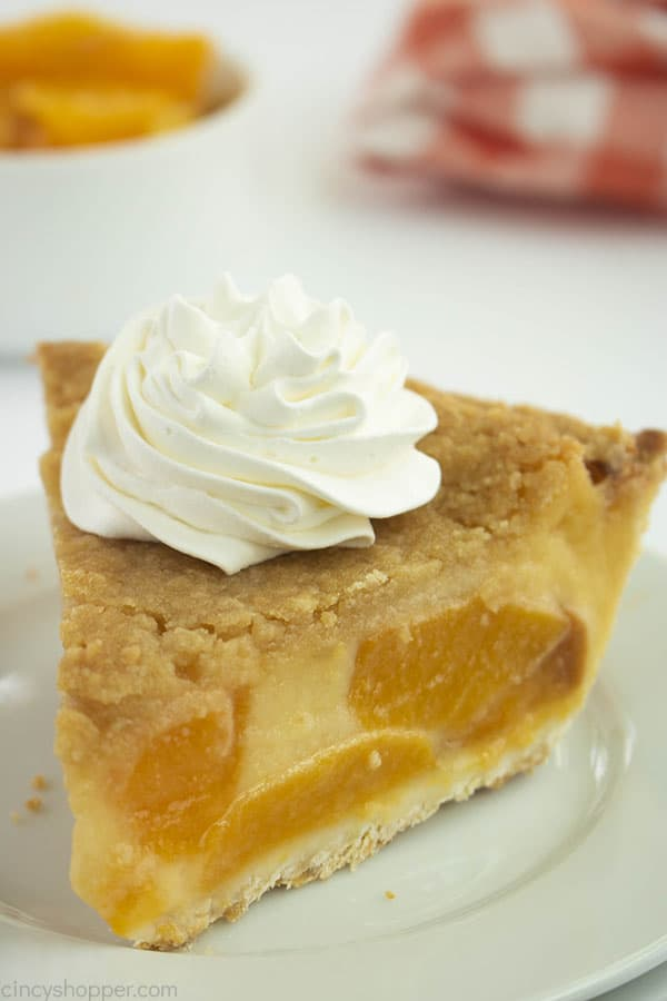 Slice of peach custard pie on a white plate with whipped topping