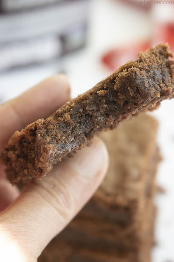 hand holding a homemade brownie with bite taken out of it