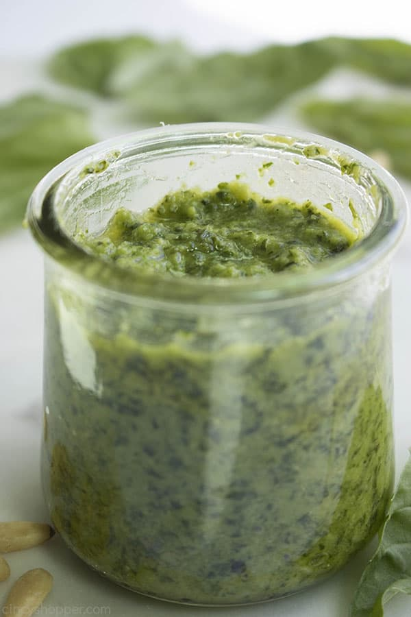 close up of green pesto in a glass jar