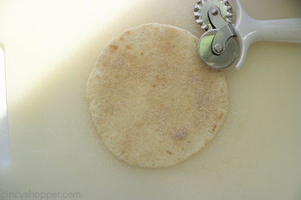 Cinnamon sugar dusted on flour tortilla with white pastry wheel