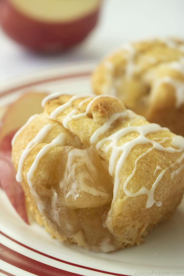Crescent Apple Pie Bites on a white and red plate with apple in background.