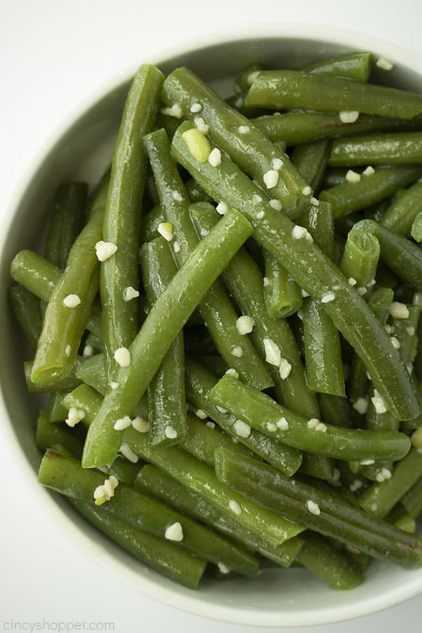 Fresh garlic green beans in a white bowl half of the bowl on white background
